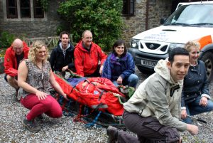 HSBC staff learn how to load and move a stretcher with members of ASSAR.